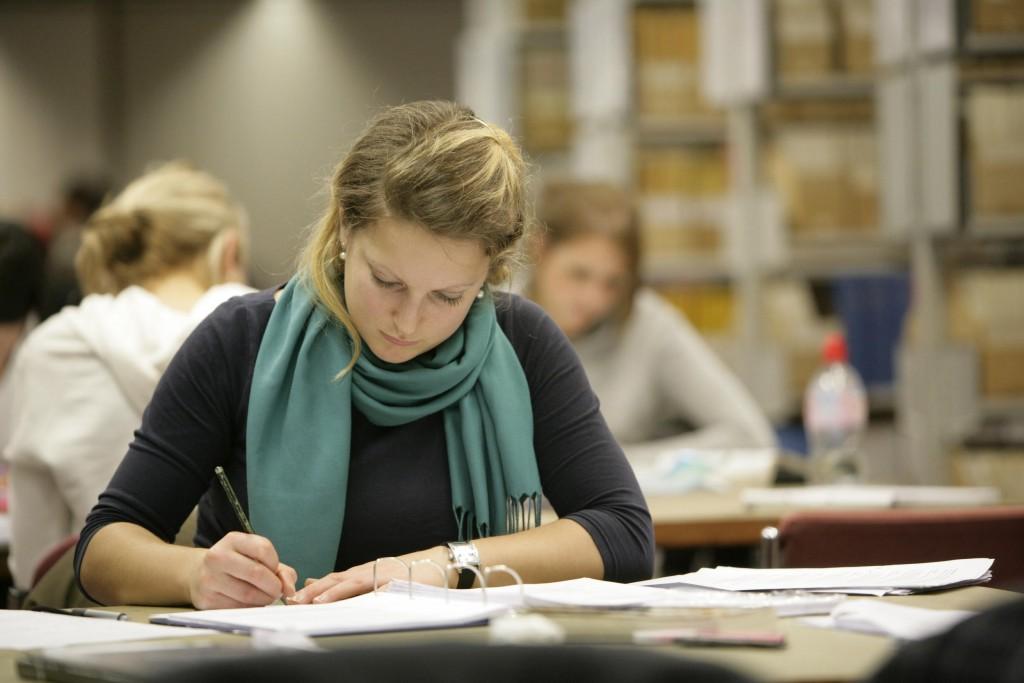 cafeaua ajuta la invatat - femeie studiu in bibliotecă