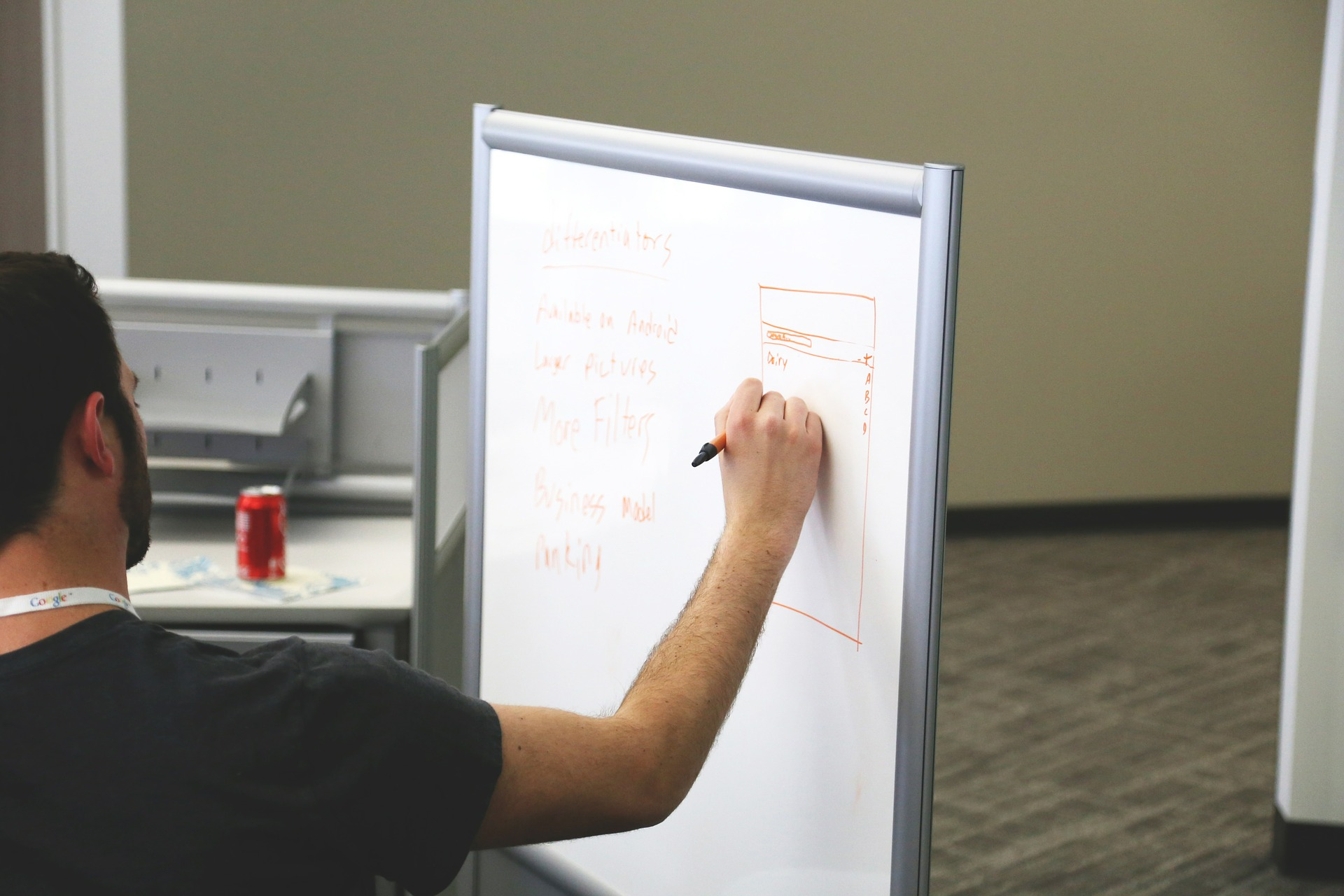 Profesor care scrie pe tabla cu marker